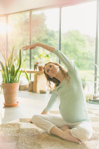Pregnant woman practicing yoga doing side stretchの写真素材 [FYI02173031]