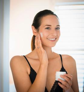 Smiling woman applying face cream to cheek in bathroom mirrorの写真素材 [FYI02173032]