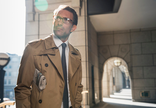 Corporate businessman in trench coat standing in sunny cloisterの写真素材 [FYI02173051]