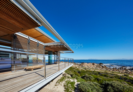 Modern luxury home showcase with ocean view under sunny blue skyの写真素材 [FYI02173078]