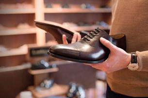 Businessman browsing dress shoes in menswear shopの写真素材 [FYI02173080]