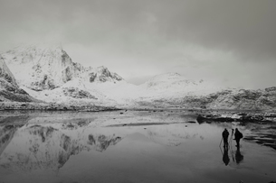 Photographers below snow covered mountains and calm bay, Norwayの写真素材 [FYI02173109]