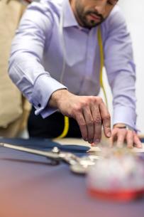 Tailor marking fabric in menswear workshopの写真素材 [FYI02173161]