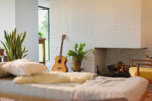 Guitar leaning near fireplace behind chaise in living roomの写真素材 [FYI02173176]