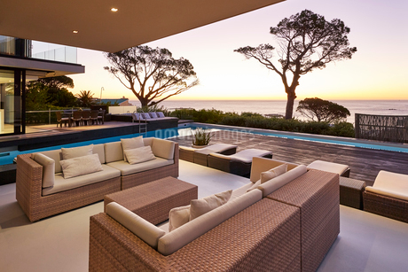 Modern luxury home showcase patio and swimming pool overlooking ocean view at sunsetの写真素材 [FYI02173177]