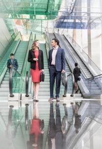 Corporate businessman and businesswoman talking below escalators in modern lobbyの写真素材 [FYI02173191]