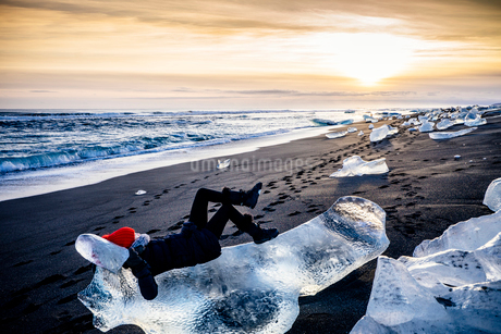 Woman laying on large ice chunk on beach at sunset, Icelandの写真素材 [FYI02173205]