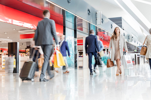 Travelers walking in airport concourseの写真素材 [FYI02173214]
