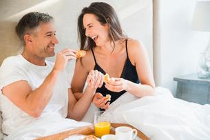 Laughing couple enjoying breakfast in bedの写真素材 [FYI02173261]