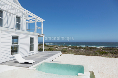 Beach house soaking pool and deck overlooking ocean under sunny blue skyの写真素材 [FYI02173268]