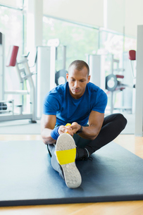 Man using resistance band to stretch leg at gymの写真素材 [FYI02173272]