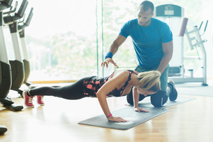 Personal trainer guiding woman doing push-ups at gymの写真素材 [FYI02173292]