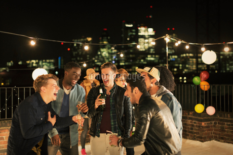 Young men drinking and laughing at rooftop partyの写真素材 [FYI02173293]