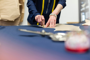Female tailor marking fabric with pattern in menswear workshopの写真素材 [FYI02173298]