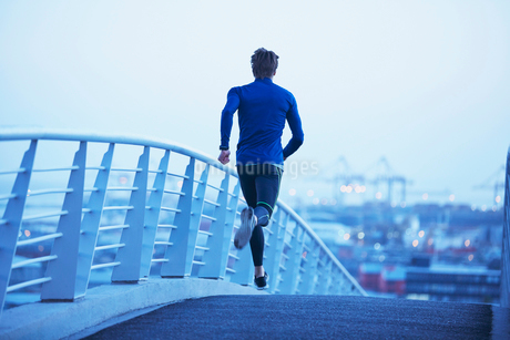 Male runner running on urban footbridge at dawnの写真素材 [FYI02173306]