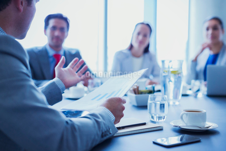 Businessman leading meeting explaining paperwork in conference roomの写真素材 [FYI02173321]