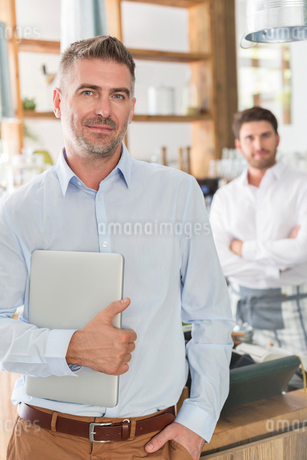 Portrait confident cafe owner with laptopの写真素材 [FYI02173341]