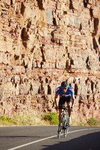 Male triathlete cyclist cycling on sunny roadの写真素材 [FYI02173378]