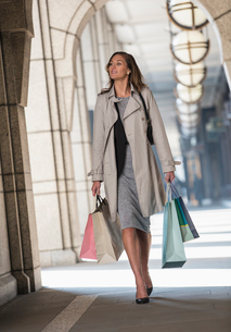 Businesswoman carrying shopping bags in cloisterの写真素材 [FYI02173384]