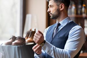 Businessman looking through window in menswear shopの写真素材 [FYI02173385]