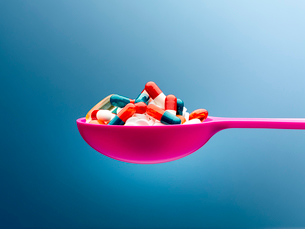 Medicine capsules in pink spoon against blue backgroundの写真素材 [FYI02173412]