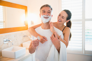 Playful wife wiping shaving cream on husband's face in bathroomの写真素材 [FYI02173421]