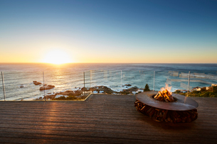 Fire pit on luxury patio with sunset ocean viewの写真素材 [FYI02173435]
