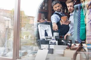 Worker showing businessman merchandise in window of menswear shopの写真素材 [FYI02173489]