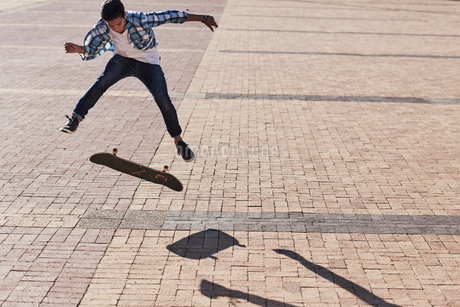 Teenage boy flipping skateboard on sunny cobblestoneの写真素材 [FYI02173491]