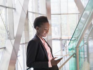 Corporate businesswoman using digital tablet in modern office lobbyの写真素材 [FYI02173509]