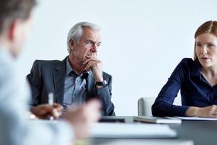 Attentive senior businessman listening to businesswoman in meetingの写真素材 [FYI02173523]