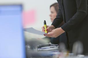 Businesswoman highlighting paperwork in officeの写真素材 [FYI02173532]