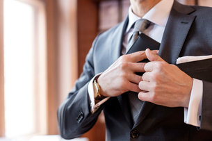 Close up businessman retrieving wallet from suit jacketの写真素材 [FYI02173534]
