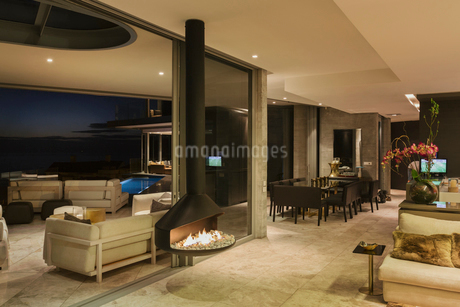 Illuminated luxury modern home showcase interior with hanging fireplaceの写真素材 [FYI02173538]