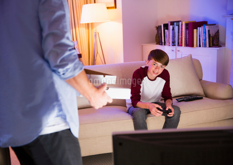 Father bringing pizza to son playing video game in living roomの写真素材 [FYI02173541]