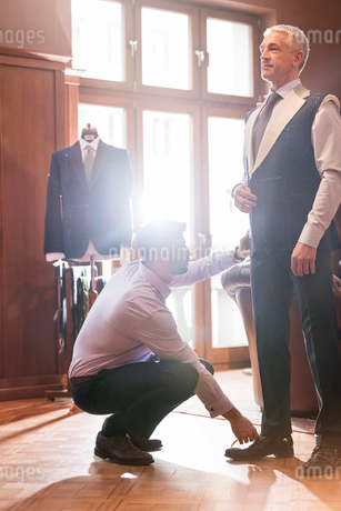 Tailor fitting businessman for suit in menswear shopの写真素材 [FYI02173551]