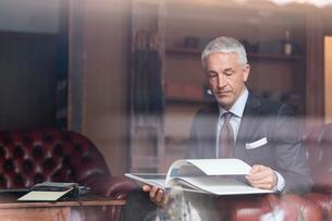 Businessman browsing book in menswear shopの写真素材 [FYI02173559]