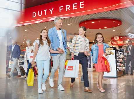 Family leaving airport duty free shop with shopping bagsの写真素材 [FYI02173563]