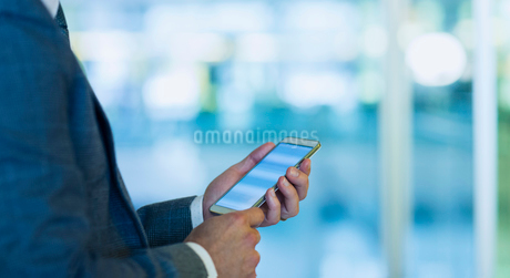 Businessman using cell phone in officeの写真素材 [FYI02173572]