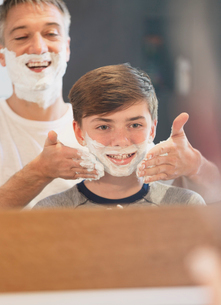 Father helping son pretending to shave in bathroom mirrorの写真素材 [FYI02173588]
