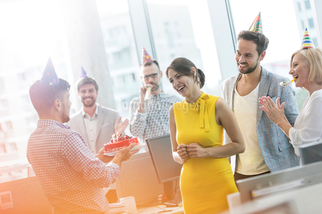 Business people celebrating birthday with cake in officeの写真素材 [FYI02173590]