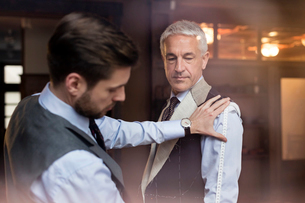 Tailor fitting businessman for suit in menswear shopの写真素材 [FYI02173594]