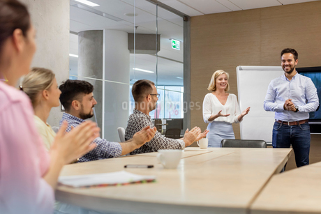 Business people clapping for businessman in conference room meetingの写真素材 [FYI02173599]