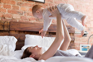 Mother lifting baby daughter overhead on bedの写真素材 [FYI02173611]