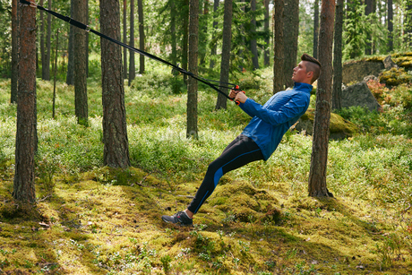 Runner using resistance band on tree in woodsの写真素材 [FYI02173643]