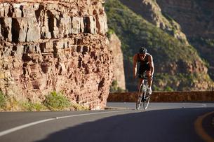 Male triathlete cycling uphillの写真素材 [FYI02173780]
