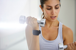 Focused woman doing biceps curls with dumbbellsの写真素材 [FYI02173783]