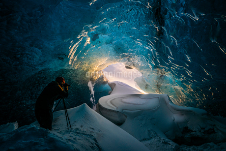 Photographer in ice cave, Icelandの写真素材 [FYI02173786]