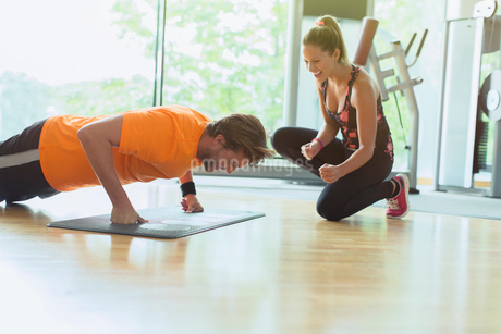 Personal trainer cheering on man doing push-ups at gymの写真素材 [FYI02173809]