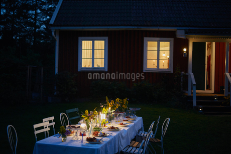 Candlelight garden party dinner outside illuminated house at nightの写真素材 [FYI02173821]
